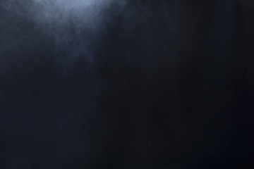 Smoke clouds create fog on left side of black background