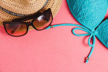 Swimsuit, Hat, Sunglasses on Pink Background. Top View Travel Concept with Copyspace.