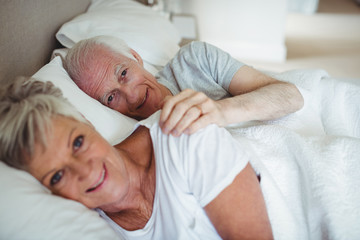 Smiling senior couple lying on bed