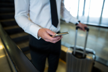 Businessman on escalator using mobile phone in airport