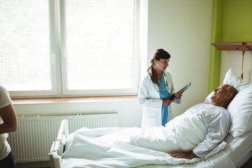 Female doctor talking with senior man in hospital