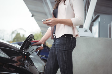 Mid section of woman using mobile phone while charging electric car