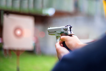 gun in hand focus aim to the target paper in background for human gun shooting practice, martial art on arm and weapon