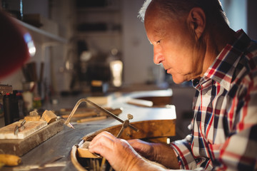 Goldsmith shaping metal with coping saw