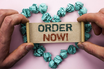 Word writing text Order Now. Business concept for Buy Purchase Order Deal Sale Promotion Shop Product Register written on Cardboard Paper Holding by man plain background on Heart Paper Balls.