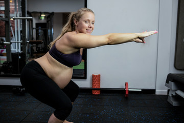 Portrait of pregnant woman performing stretching exercise