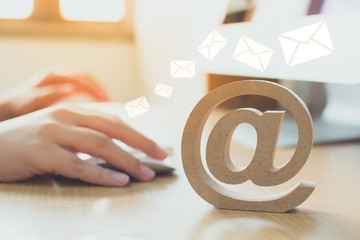 Email marketing concept, Hand using computer sending message with wooden email address symbol and...