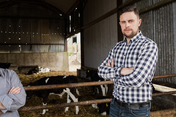 Man standing by fence at barn