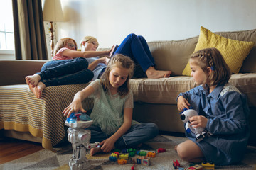 Siblings playing with toys in living room