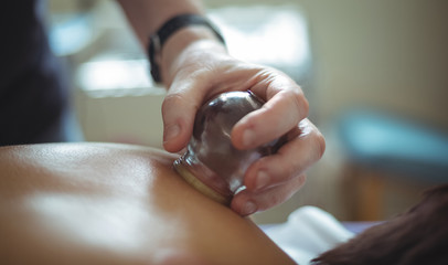 Close-up of therapist giving cupping therapy to man