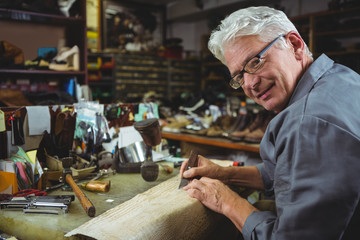 Portrait of shoemaker cutting a piece of material