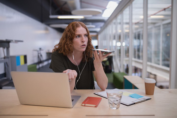 Female executive talking on mobile phone at desk