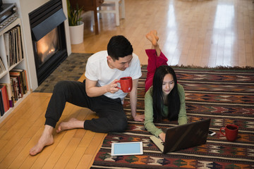 Couple using laptop near fireplace in living room