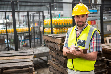 Smiling male worker noting about products in warehouse