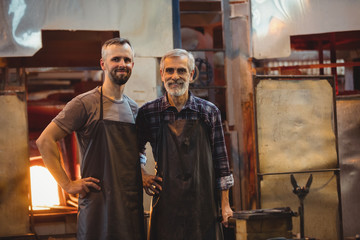 Portrait of team of glassblowers with hands on hip