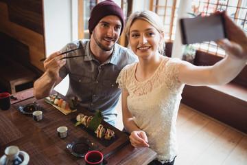 Couple taking selfie while having sushi
