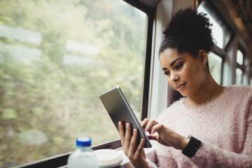 Young woman using digital tablet in train