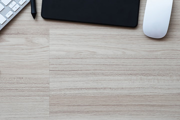 Graphic design office desk workplace with coffee cup, notepad and glasses on wooden background. Top view with copy space