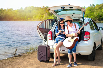 Couple of traveler sitting on hatchback of car and looking at the picture on camera near the lake during holiday.Young couple tourist enjoying on vacation.