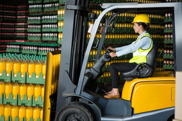 Confident female worker driving forklift in warehouse