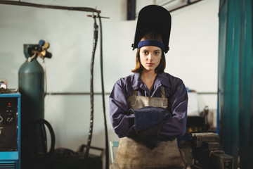 Portrait of female welder standing with arms crossed