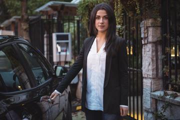 Portrait of beautiful woman standing near car