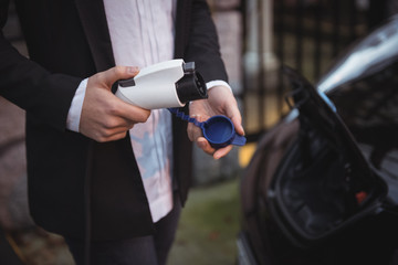 Woman holding car charger at electric vehicle charging station