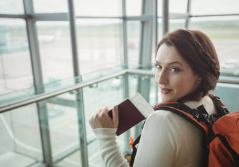 Portrait of woman with passport standing in waiting area