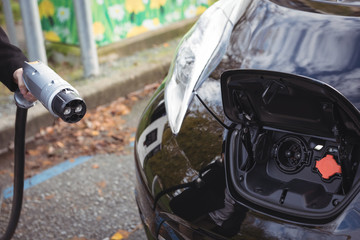 Man holding car charger at electric vehicle charging station