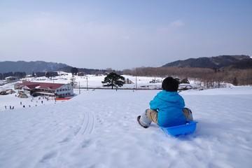 スキー場でソリ遊びをする子供