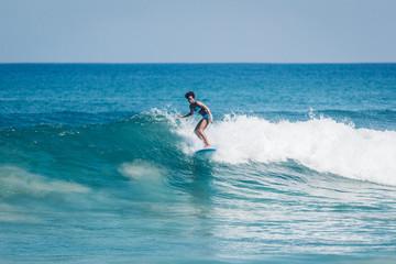 Pacific islander surfer girl with afro surfing on longboard in Padang Padang beach, Bali