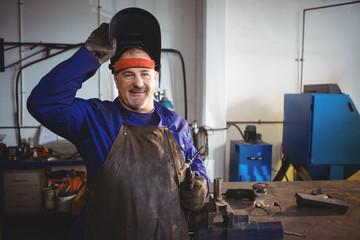 Welder holding welding machine in workshop