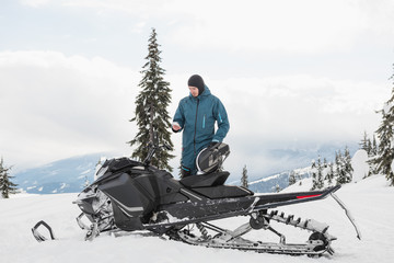Man using mobile phone while standing near snowmobile in snowy alps