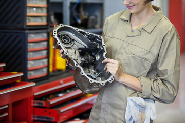 Female mechanic holding spare parts