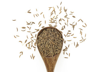 Cumin seeds in wooden spoon on a white background. Top view.