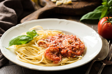 Spaghetti with tomato sauce and shrimps on white plate. Closeup view. Italian cuisine meal