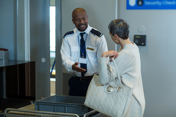 Commuter getting a bag checked from airport security officer