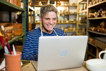 Happy male potter using laptop