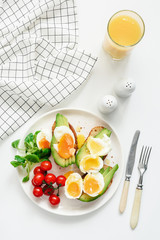 Healthy avocado and egg toasts and orange juice for breakfast on white background. Top view, flat lay, modern healthy lifestyle