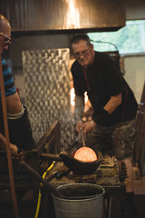 Team of glassblowers forming and shaping a molten glass