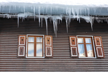 Large icicles hang from the roof of the house in the Alps