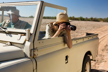 Woman by man photographing while traveling in off road vehicle