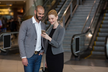 Couple using mobile phone at airport