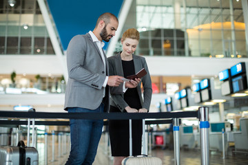 Businesspeople checking their passport at check-in counter
