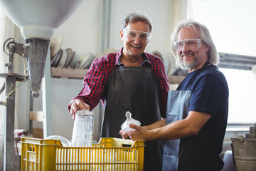 Portrait of glassblower and a colleague holding glassware
