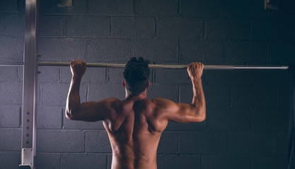 Muscular man exercising on pull-up bar