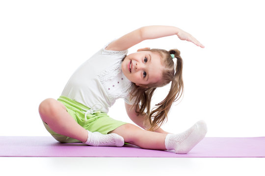 Child girl practicing yoga, stretching in exercise wearing sportswear. Kid isolated over white background