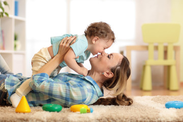 Woman with child one year old playing on cozy carpet in living room