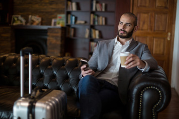 Thoughtful businessman holding mobile phone and coffee cup in waiting area