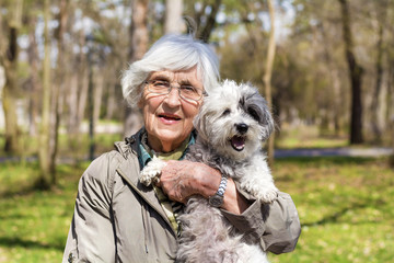 Beautiful Happy Senior Woman Hugging her Cute Dog Outdoor